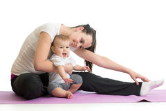 Young woman mother doing fitness exercises with baby, studio portrait isolated on white background Royalty Free Stock Photo