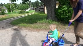 Young woman mother pushing blond toddler girl on small tricycle. stock footage