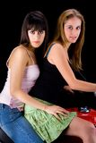 Young woman on motor bike. Two attractive young woman on motor bike with black studio background stock photography