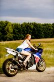 Young woman with a motorcycle speed Stock Image