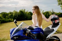 Young woman with a motorcycle speed. Beautiful young woman with a motorcycle speed in nature Stock Photography