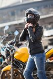 Young woman motorcyclist buttons black crash helmet for riding bike on urban road. S Stock Images