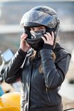 Young woman motorcyclist put on crash helmet for riding bike on urban road Royalty Free Stock Photo
