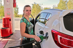 Young woman-motorist fills her car with benzine at gas station. Young beautiful woman-motorist fills her car with benzine at gas station Royalty Free Stock Photography