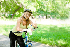 Young woman with mountain bike and bottle of water in hand Stock Images