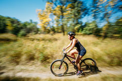 Young woman mountain Bike cyclist riding track at sunny day, hea Royalty Free Stock Photos