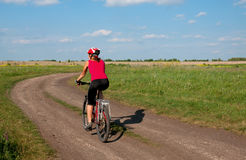 Young woman mountain bike ride on  dirt road Royalty Free Stock Images