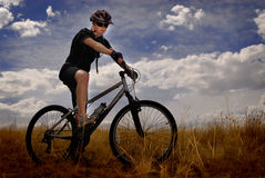 Young Woman Mountain Biking Royalty Free Stock Photography