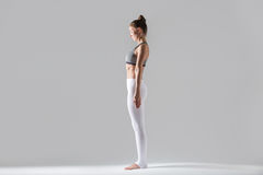 Young woman in mountain pose, grey studio background. Young slim woman practicing yoga, standing in mountain exercise, Tadasana pose, working out wearing Royalty Free Stock Photography
