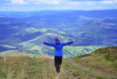 Young woman on the mountain with raised hands Stock Photo