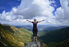 Young woman on the mountain with raised hands Stock Photos