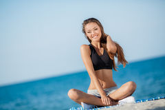 The young woman moves training on a beach. Stock Photo