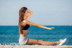 The young woman moves training on a beach. Royalty Free Stock Image