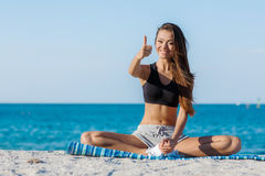 The young woman moves training on a beach. Stock Photos