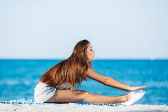 The young woman moves training on a beach. Royalty Free Stock Images