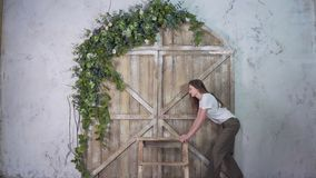 Young woman moves vintage stepladder on the background of beautiful gate with flowers stock photos