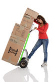 Young woman moving boxes with with a hand truck or dolly. NShot on a white background Royalty Free Stock Photo