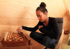 Young woman moving with chessman in chess Royalty Free Stock Images