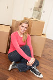 Young woman on moving day sitting on floor Royalty Free Stock Images