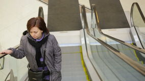 Young woman on moving escalator stock video footage
