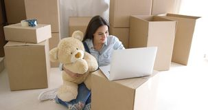 Young woman moving house with her teddy bear stock video footage