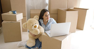 Young woman moving house with her teddy bear Stock Photo
