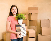 Young woman moving house to college, holding pile books and plan Stock Photos