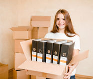 Young woman moving house to new home holding cardboard boxes Royalty Free Stock Photos