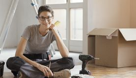 Free Young Woman Moving In Her New House And Doing A Home Makeover Stock Photography - 130199422