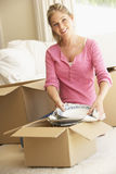 Young Woman Moving Into New Home Unpacking Boxes Stock Photo