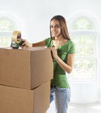 Young woman moving to a new home. Happy young woman moving boxes from old home to a new home and is taping and packing or unpacking boxes. Soft background Stock Images