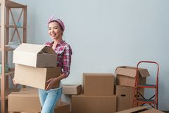 Young girl moving to new place walking holding boxes looking camera cheerful stock photography