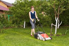 Young woman mow grass. Young woman with electric lawn-mower Royalty Free Stock Photo