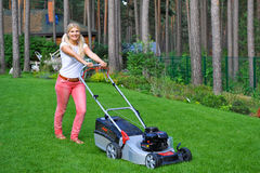Young woman mowing grass. In her garden Royalty Free Stock Photo