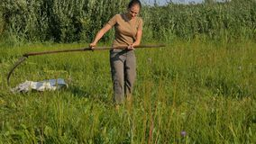 Young woman mowing the green grass with the scythe on the summer field by the river. Beautiful landscape. Work in the. Field. Real rural woman stock footage