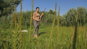 Young woman mowing the green grass with the scythe on the summer field by the river. Beautiful landscape. Work in the. Field. Real rural woman stock video footage