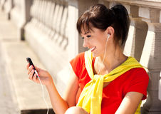 Young woman with mp3 player, smiling Stock Photo