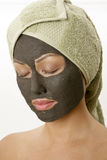 Young woman with mud facial mask Stock Image