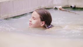 Young woman with mud mask on skin face relaxing in mineral mud in outdoor spa. Beautiful woman swimming in thermal bath.  stock footage