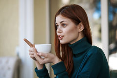 Young woman with a mug of coffee in a cafe on the veranda stock photos