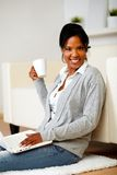 Young woman with a mug in front of her laptop Royalty Free Stock Photo