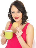 Young Woman with a Mug of Tea and Biscuit Royalty Free Stock Image