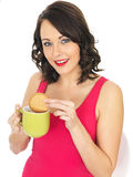 Young Woman with a Mug of Tea and Biscuit Royalty Free Stock Photography