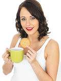 Young Woman with a Mug of Tea and Biscuit Royalty Free Stock Photo