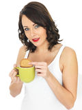Young Woman with a Mug of Tea and Biscuit Royalty Free Stock Photos
