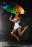 Young woman with multi-coloured umbrella. Royalty Free Stock Images