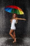 Young woman with multi-coloured umbrella. Young pretty woman with multi-coloured umbrella under rain on a black background royalty free stock photos