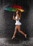 Young woman with multi-coloured umbrella. Young pretty woman with multi-coloured umbrella under rain on a black background stock photo