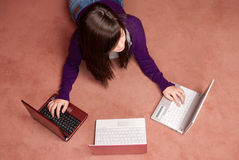 Young woman multitasking three laptop lying royalty free stock photo