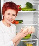 Woman against the refrigerator Stock Photos
